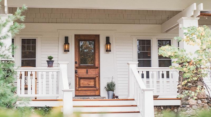 The beautifully renovated porch features new center stairs, railing, and vintage style lighting