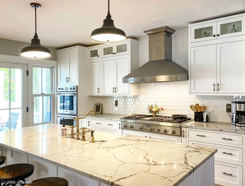 Renovated kitchen with custom cabinets, marble counters and classic brass pulls & switchplates