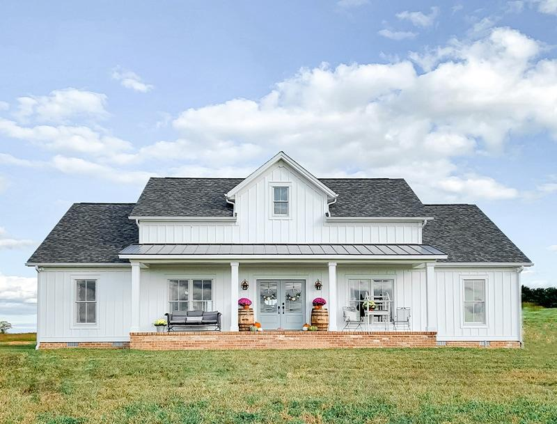 Quintessential farmhouse style, with board & batten siding, broad front porch and setting amid open fields
