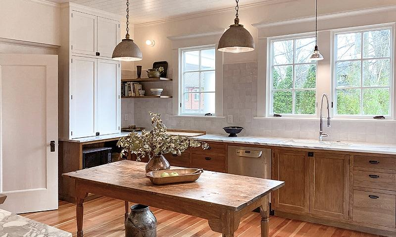 Newly recreated kitchen in a 1909 home features bronze bin pulls and latches, and vintage pendant lighting