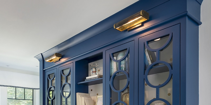 Brass picture light mounted over built-in bookcase